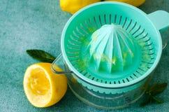 Citrons et menthe frais avec le presse-fruits d'agrume sur le fond de turquoise Copiez l'espace Photos stock
