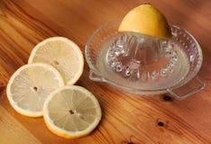 Citrons et presse-fruits sur la surface de travail Photo stock