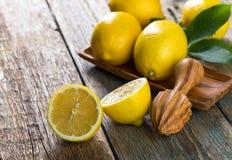 Citrons et vieux presse-fruits en bois image stock