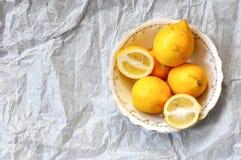 Citrons frais dans un plat de porcelaine de cru, côté droit, sur un fond blanc image stock