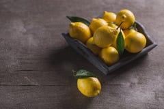 Citrons jaunes juteux frais avec des feuilles sur la table en bois images stock