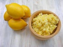 Citrons jaunes sur un fond en bois minable blanc avec la purée des citrons dans le pot en bois Images stock