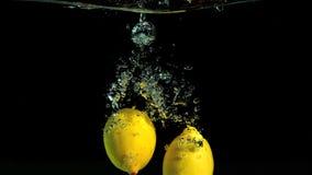 Citrons se laissant tomber dans l'eau clips vidéos