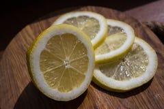 Citronskivor på mörk skärbräda Royaltyfria Foton