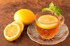 Citronte - koppen av citronskivor med te och mintkaramellen spricker ut arkivfoto