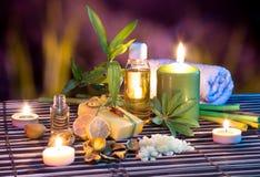 Citrontvål, olja, handduk, salt, bambu och stearinljus i trädgård fotografering för bildbyråer