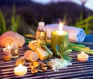 Citrontvål, olja, handduk, saltar och stearinljus i trädgård arkivfoto