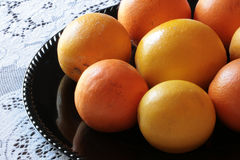 Citrus. Oranges and Meyer lemons arranged in a circular pattern on a shiny black plate Royalty Free Stock Photos
