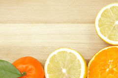 Citrus border on wooden table Royalty Free Stock Image