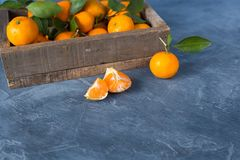 Citrus. Bright ripe tangerines with green leaves in a wooden bo royalty free stock photos