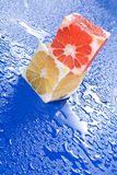 Citrus cubes on wet surface Royalty Free Stock Photography