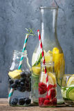Citrus cucumber sassy water. Citrus cucumber berries blueberry and raspberry sassy sassi water for detox in glass bottles with cocktail tubes on wooden blue Stock Photos