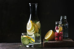 Citrus cucumber sassy water. Citrus cucumber berries blueberry and raspberry sassy sassi water for detox in glass bottles on dark black background. Clean eating Stock Photos