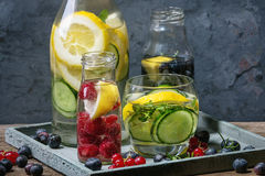 Citrus cucumber sassy water. Citrus cucumber berries blueberry and raspberry sassy sassi water for detox in glass bottles on wooden blue background. Clean eating Royalty Free Stock Image