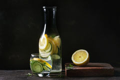 Citrus cucumber sassy water. Citrus cucumber sassy sassi water for detox in glass bottle on dark black background. Clean eating, healthy lifestyle concept Stock Photo