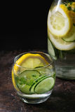 Citrus cucumber sassy water. Citrus cucumber sassy sassi water for detox in glass bottle on dark black background. Clean eating, healthy lifestyle concept Stock Images