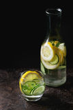 Citrus cucumber sassy water. Citrus cucumber sassy sassi water for detox in glass bottle on dark black background. Clean eating, healthy lifestyle concept Stock Image