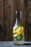 Citrus cucumber sassy water. Citrus cucumber sassy sassi water for detox in glass bottle on wooden background. Clean eating, healthy lifestyle concept, sunlight Stock Photo