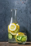 Citrus cucumber sassy water. Citrus cucumber sassy sassi water for detox in glass bottle on wooden blue background. Clean eating, healthy lifestyle concept Stock Photos
