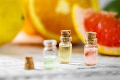 Citrus essential oil bottles on fruit background. Small citrus essential oil bottles on fruit background stock photo