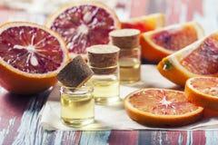 Citrus för nödvändig olja med orange skivor, i glasflaska på ol Arkivbilder