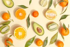Citrus food on ligth-yellow background - assorted citrus fruits with mint leaves. Top view. Mix lemon orange whole organic lime slice cut half cross collection royalty free stock photos