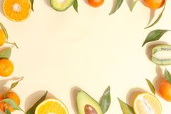 Citrus food on ligth-yellow background - assorted citrus fruits with mint leaves. Top view. Mix lemon orange whole organic lime slice cut half cross collection royalty free stock photo