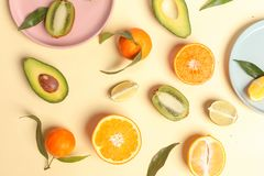 Citrus food on ligth-yellow background - assorted citrus fruits with mint leaves. Top view. Mix lemon orange whole organic lime slice cut half cross collection stock image
