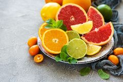 Citrus fresh fruits. Plate with citrus fresh fruits on a concrete background royalty free stock photography