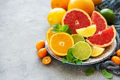Citrus fresh fruits. Plate with citrus fresh fruits on a concrete background stock image