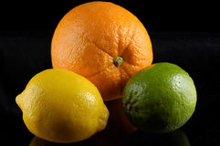 Citrus Fruit. An Orange, lemon, and lime seem to float in a black background Royalty Free Stock Images