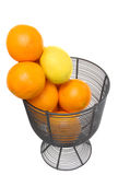 Citrus Fruit. Oranges and a lemon drop into a wire basket Royalty Free Stock Photo