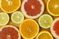 Citrus fruit background with sliced f oranges lemons lime tanger Stock Photos
