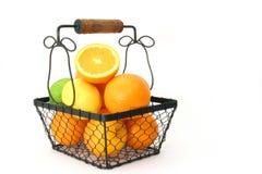 Citrus Fruit In A Basket Over White. Citrus fruit in a wire basket over white Royalty Free Stock Images