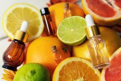 Citrus fruit essential oils and cosmetics. Citrus fruit essential oils and fresh fruits royalty free stock photography