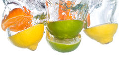 Citrus fruit falling in water. Citrus fruit falling into clear water royalty free stock images