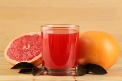 Citrus fruit. Fresh grapefruit with leaves and juice on a natural wooden table. close-up stock photos