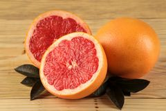 Citrus fruit. Fresh grapefruit with leaves on a natural wooden table. close-up royalty free stock photo