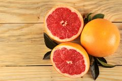 Citrus fruit. Fresh grapefruit with leaves on a natural wooden table. top view royalty free stock photo