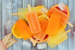 Citrus fruit popsicles, above view on rustic wood. Group of citrus fruit popsicles, above view on a rustic wood background Stock Image