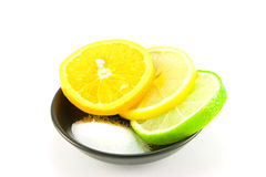 Citrus Fruit and Salt. Slice of lemon, lime and orange in a small black dish with salt on a white background Royalty Free Stock Photos