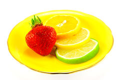 Citrus Fruit and Strawberry. Slice of lemon, lime and orange with a red juicy strawberry on a fancy yellow plate with a white background Royalty Free Stock Photos
