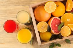 Citrus fruit. various citrus fruits with leaves of lemon, orange, grapefruit in a box and juices on a natural wooden table. top vi. Citrus fruit. various citrus royalty free stock photos