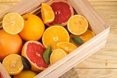 Citrus fruit. various citrus fruits with leaves of lemon, orange, grapefruit in a box on a natural wooden table stock photo