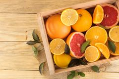 Citrus fruit. various citrus fruits with leaves of lemon, orange, grapefruit in a box on a natural wooden table. top view royalty free stock photography