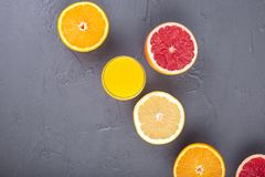 Citrus fruits with assorted slices and juice in a glass. Gray stone background. Vitamins and health in food. Copy space royalty free stock photography