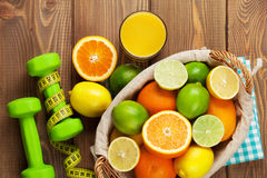 Citrus fruits in basket and dumbells. Oranges, limes and lemons Royalty Free Stock Image