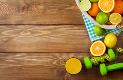 Citrus fruits in basket and dumbells. Oranges, limes and lemons Royalty Free Stock Photo