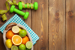 Citrus fruits in basket and dumbells. Oranges, limes and lemons Stock Images