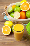 Citrus fruits in basket and glass of juice. Oranges, limes and l Royalty Free Stock Photography